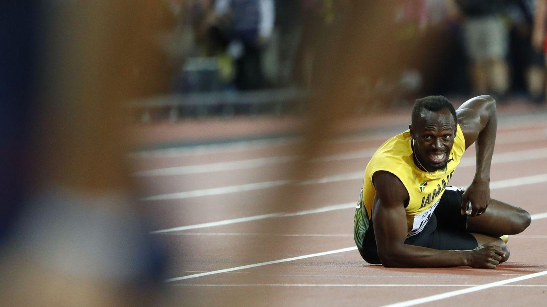 Bolt observa desde el suelo el final de la carrera de relevos. (EFE)