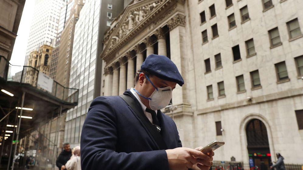 Foto: Un hombre con mascarilla frente a la fachada de Wall Street. (Reuters)