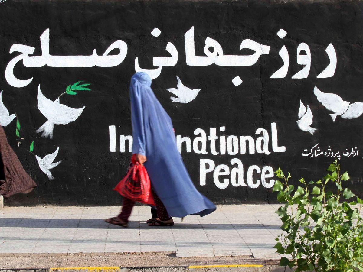 Foto: Una mujer frente a un mural en Herat, Afganistán. (EFE)