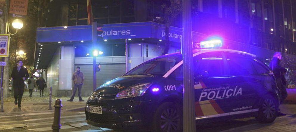 Un coche de Policía, en el exterior de la sede del PP. (Efe).