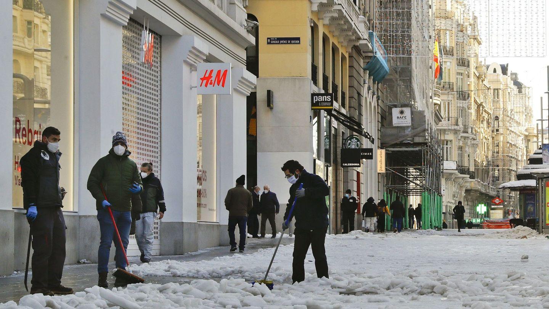 Varias personas limpian la nieve de los comercios de la Gran Vía en Madrid. (EFE)