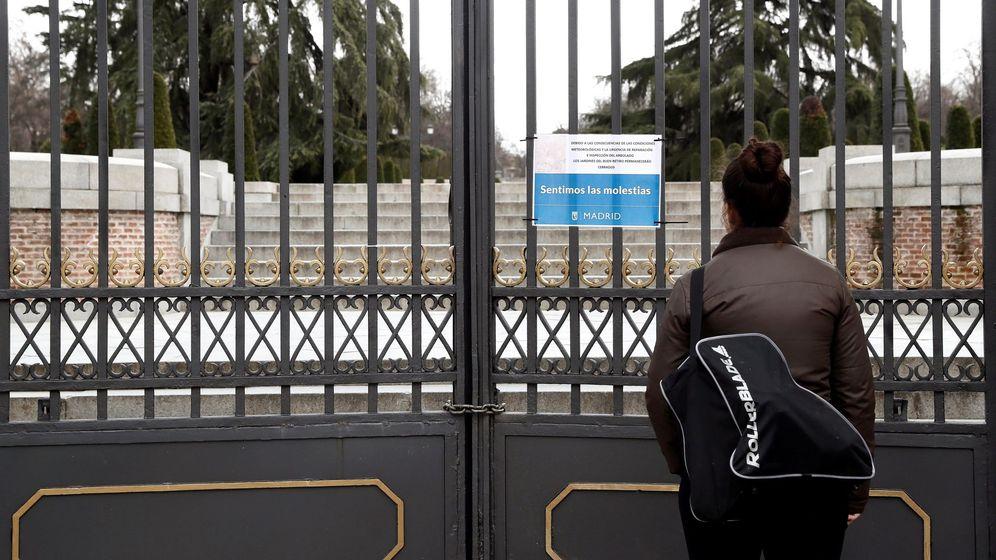 Foto: Una mujer observa un cartel alusivo al cierre del parque del Retiro de Madrid. (EFE)