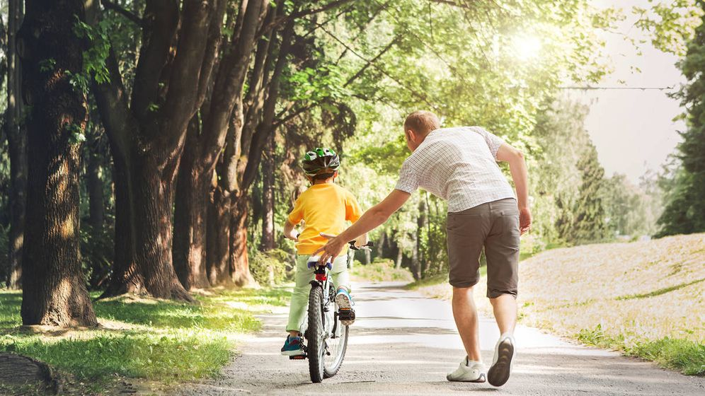 Foto: Un padre enseña a montar en bicicleta a su hijo. (iStock)