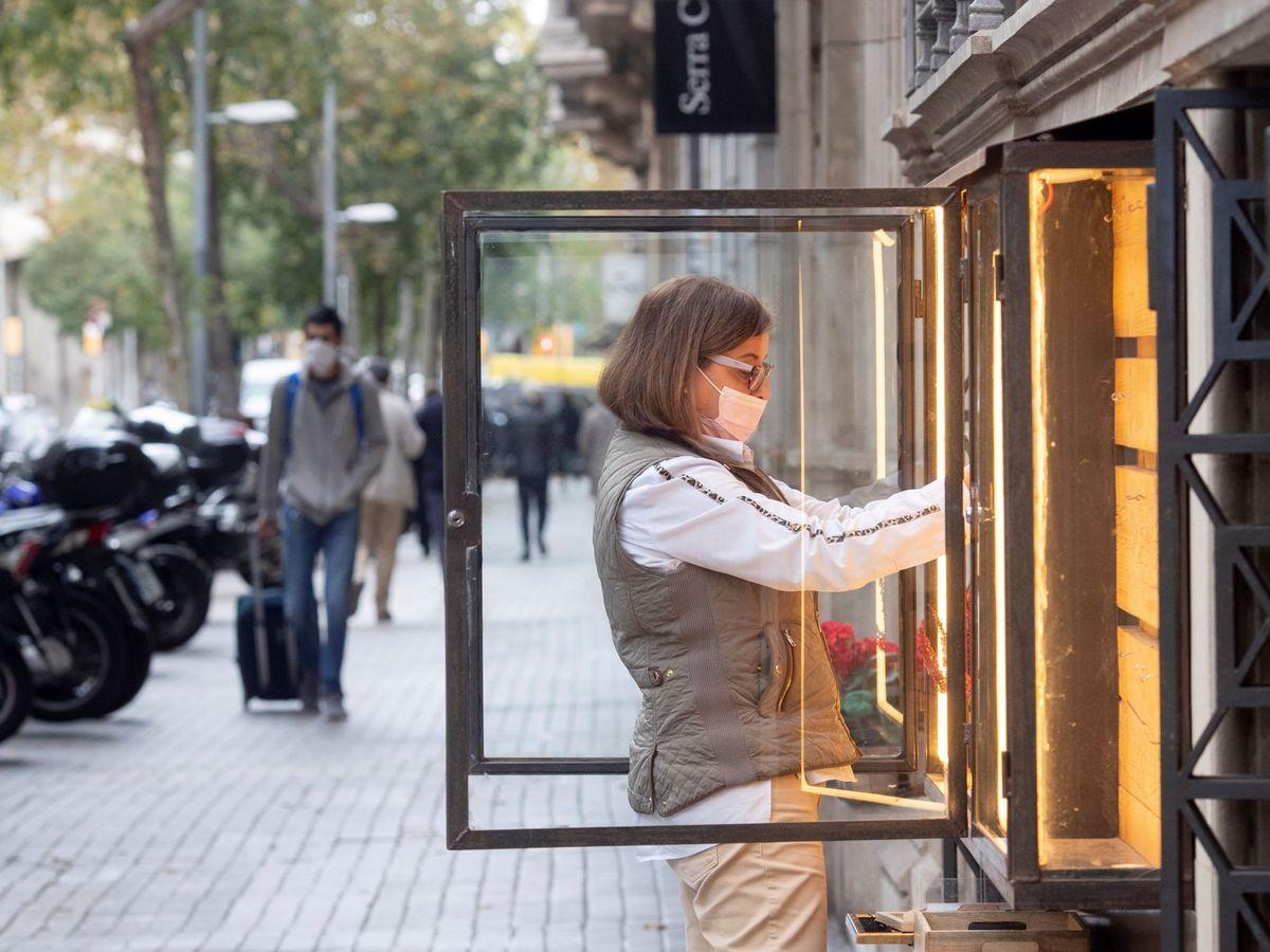 Foto: Una mujer ordena un escaparate en una tienda del centro de Barcelona. (EFE)