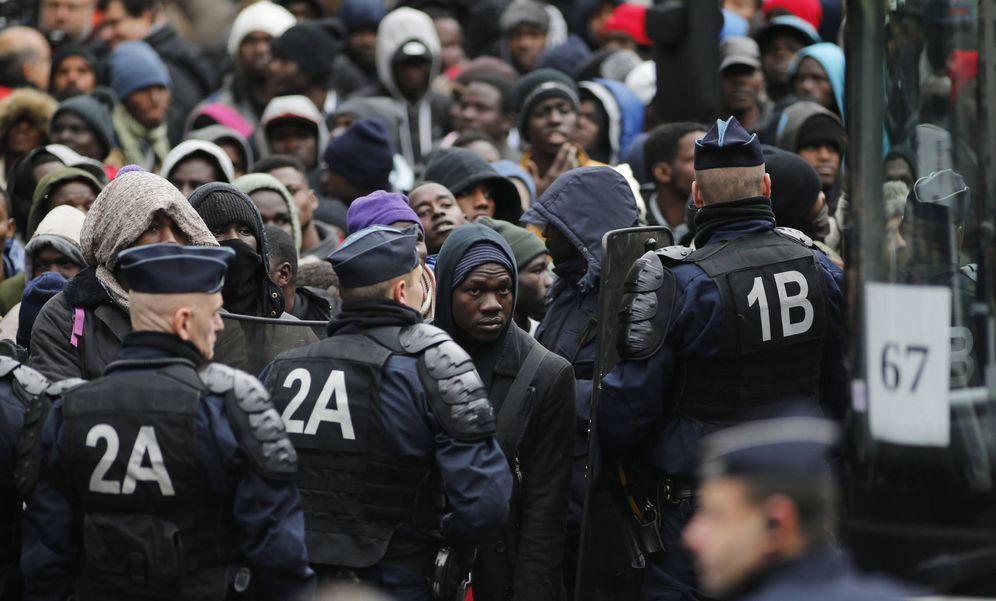 Foto: Agentes de policía franceses ante migrantes transferidos por las autoridades a centros de detención, en París (Reuters).