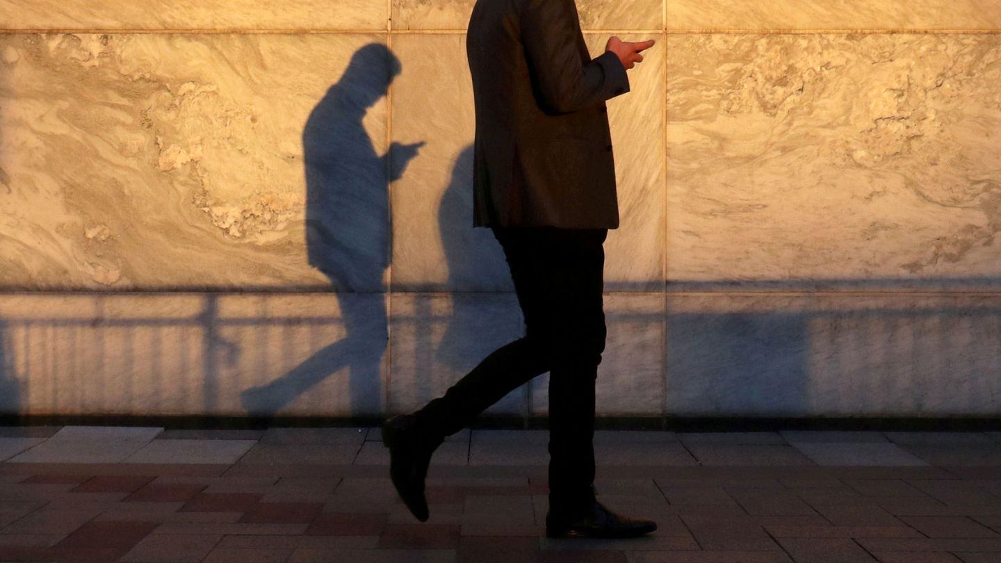 FILE PHOTO: An unidentified man using a smart phone walks through London's Canary Wharf financial district in the evening light in London, Britain, September 28, 2018.   REUTERS Russell Boyce File Photo
