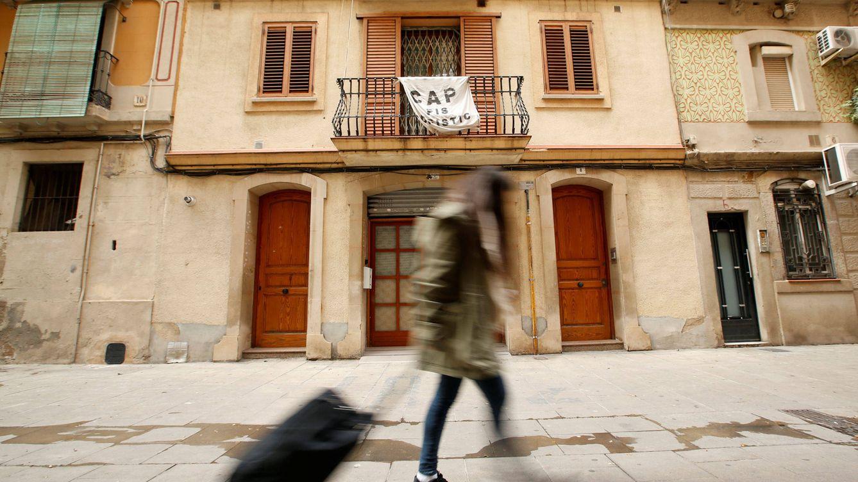 Foto: Una joven sostiene su maleta frente a una pancarta contra Airbnb. (Reuters)