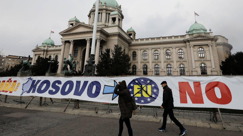 Varias personas pasan ante una pancarta ante el Parlamento serbio, en Belgrado, en marzo de 2018. (Reuters)
