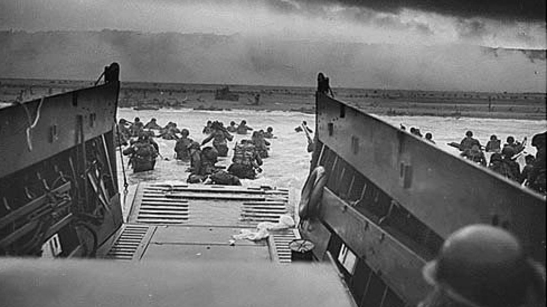 Fotografía facilitada por el ejército de los EEUU que muestra a soldados que esquivan fuego enemigo durante el desembarco de Normandía (Francia).