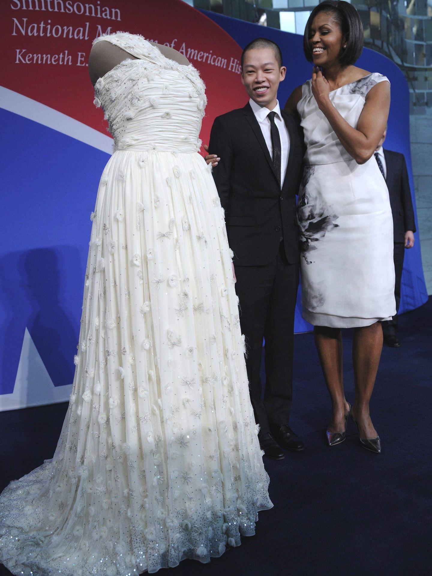 Michelle Obama y el diseñador Jason Wu,  junto al vestido que lució durante los bailes inaugurales de la presidencia de su marido. (EFE)