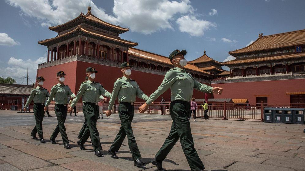 Foto: Soldados del Ejército Popular de Liberación de China (PLA) con máscaras protectoras marchan más allá de la entrada a la Ciudad Prohibida en Pekín (EFE)