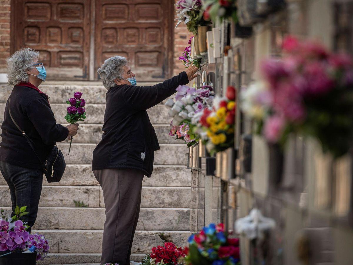Foto: Dos mujeres colocan flores en una tumba del cementerio de Alcalá. (EFE)