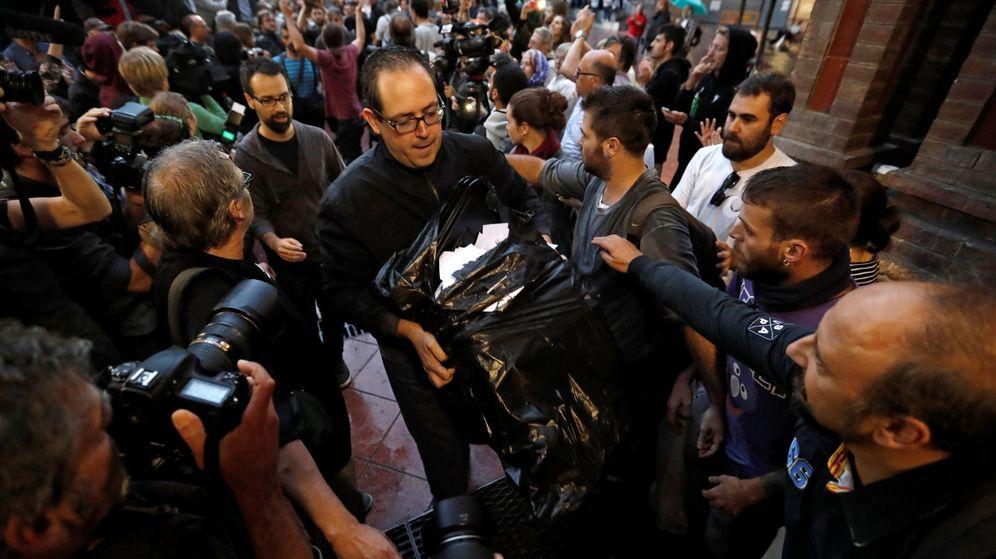 Foto: Un hombre lleva las papeletas a un centro de votación en Barcelona. ((Reuters)