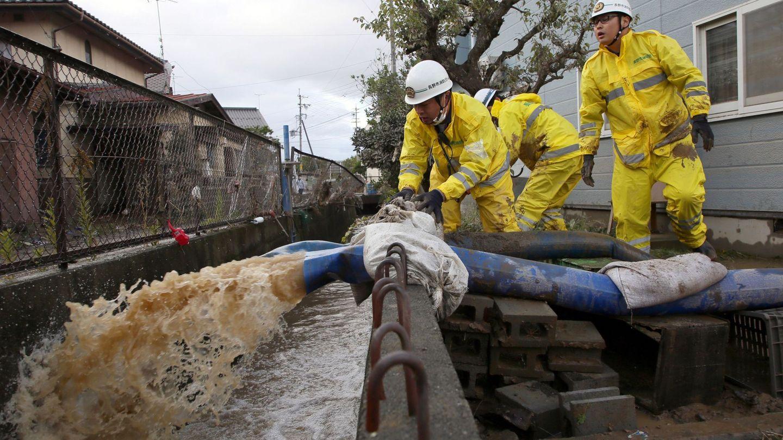 Varios operarios del servicio de emergencia ayudan a achicar agua. (EFE)