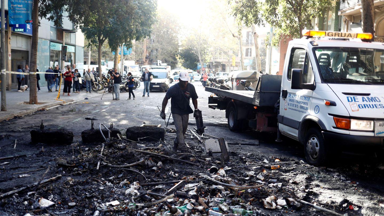 Un operario de limpieza recoge los destrozos de la noche del miércoles en Barcelona. (Reuters)