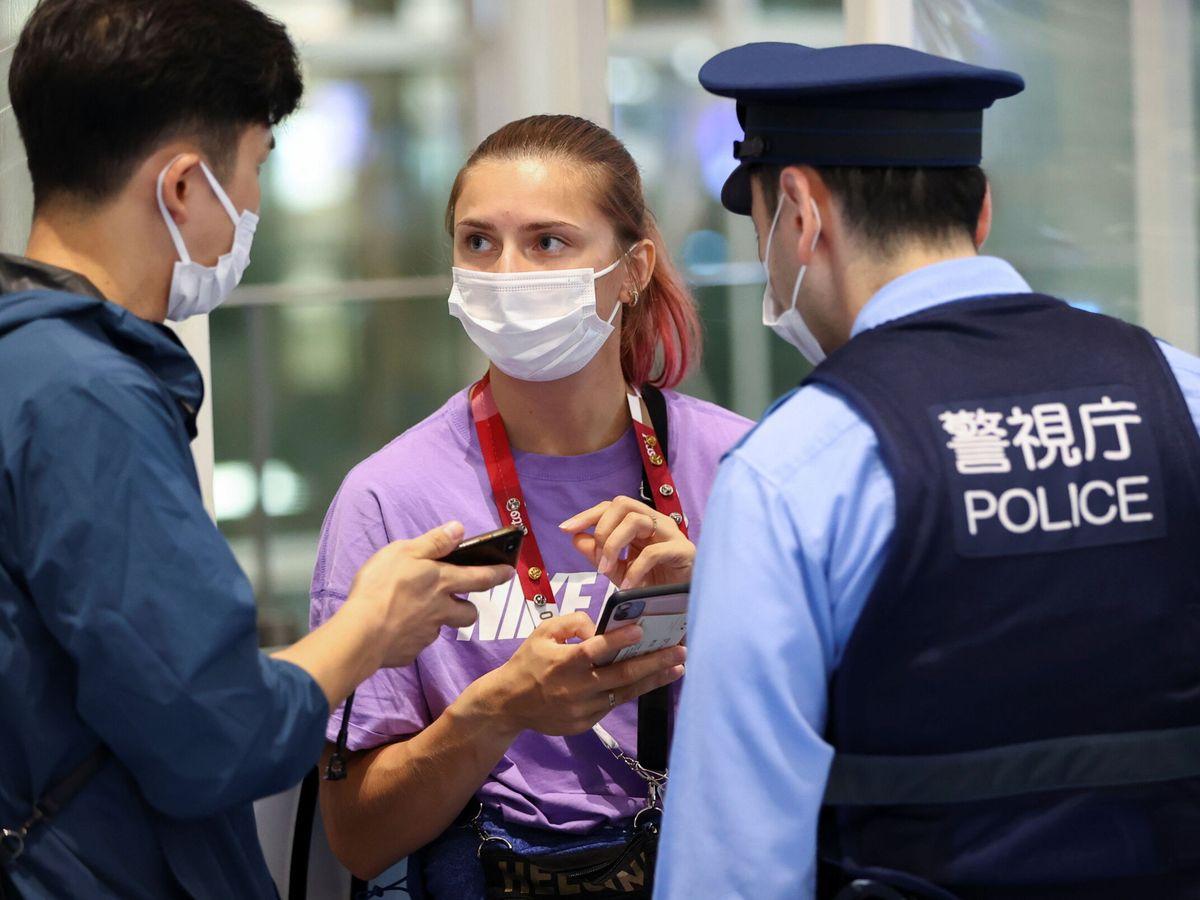 Foto: La atleta bielorrusa Krystsina Tsimanouskaya, en el aeropuerto de Haneda, junto a la policía japonesa. (Reuters)