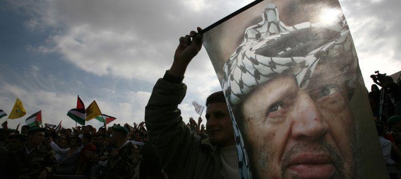 Foto: Un palestino sostiene una bandera con el rostro de Yaser Arafat en Ramala, en una imagen de archivo. (Reuters)