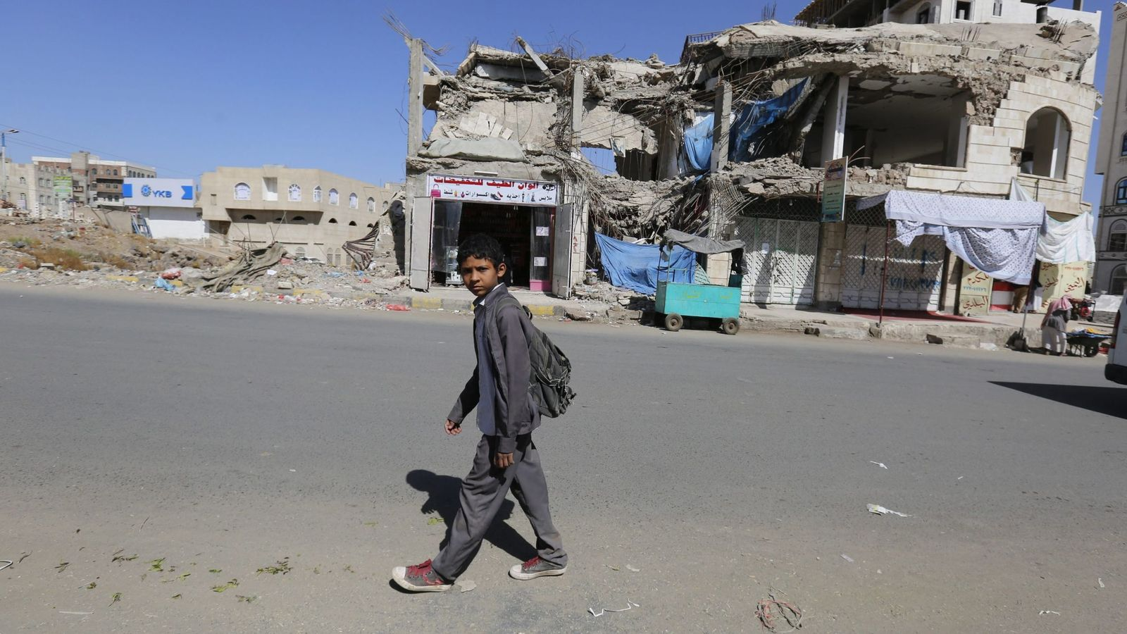 Foto: Un niño pasa ante un edificio destrozado por los bombardeos en Saná, Yemen, tras un ataque de la coalición liderada por Arabia Saudí. (EFE)