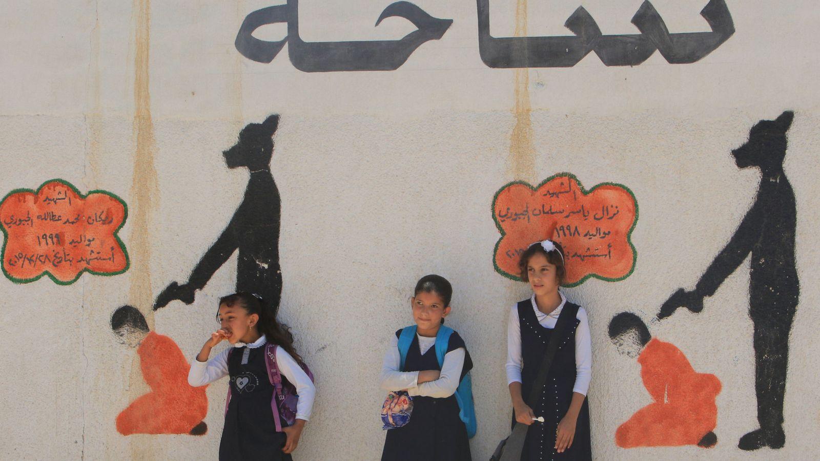 Foto: Niñas iraquíes frente a un muro escolar con dibujos de ejecuciones de prisioneros por el Estado Islámico, en Mosul, el 30 de abril de 2018. (Reuters)