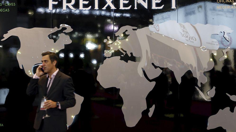 Foto: Un hombre habla por teléfono delante de un cartel de Freixenet. (Reuters)