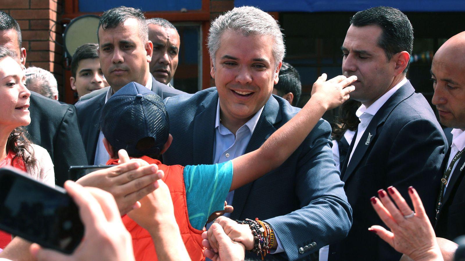 Foto: El candidato presidencial Iván Duque (d) saluda a sus simpatizantes a su llega a su puesto de votación hoy, domingo 17 de junio de 2018, en Bogotá. (EFE)