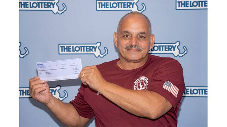 Juan McFaline, recibiendo su cheque (Lotería de Massachusetts)