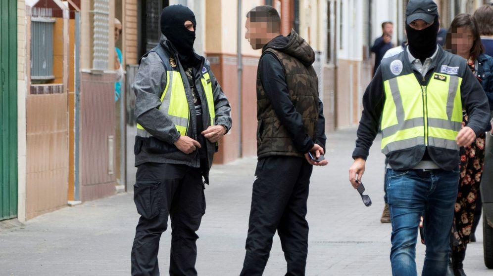 Foto: Dos agentes de la Policía Nacional caminan y hablan con algunas personas durante el registro de la casa en la que vivía el presunto yihadista. (EFE)