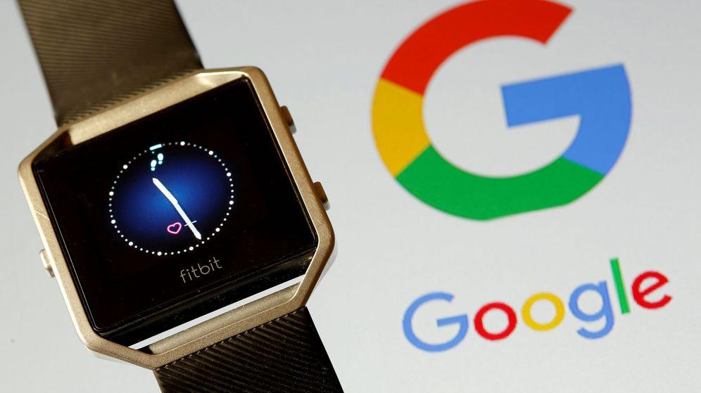 Foto: Un dispositivo de Fitbit, junto al logo de Google. (Reuters)