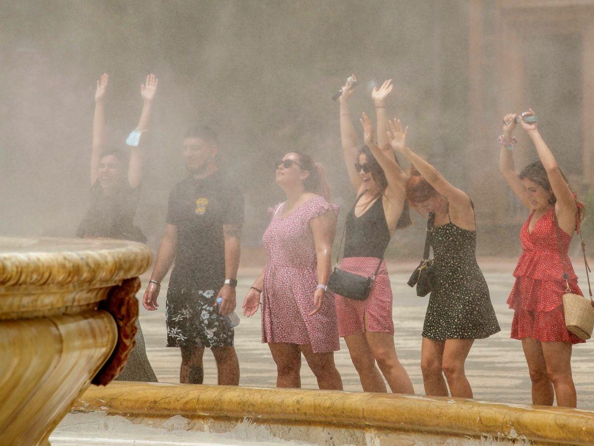 Foto: Unos turistas se refrescan con el agua que desprende la fuente de la plaza de España de Sevilla. (EFE)