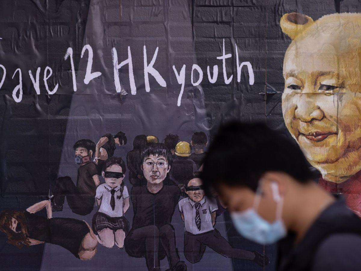 Foto: Un estudiante con mascarilla pasa delante de un mural pintado en la Universidad de Hong Kong que recuerda a 12 hongkoneses detenidos en la ciudad china de Shenzhen. (EFE)
