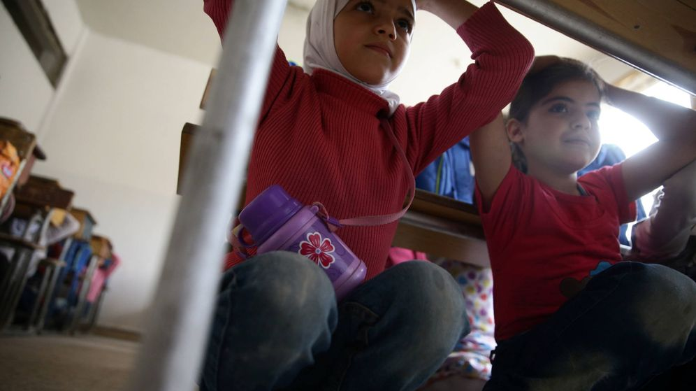 Foto: Dos niñas durante una campaña de seguridad ante ataques aéreos, en Duma, en manos de los rebeldes. (Reuters)