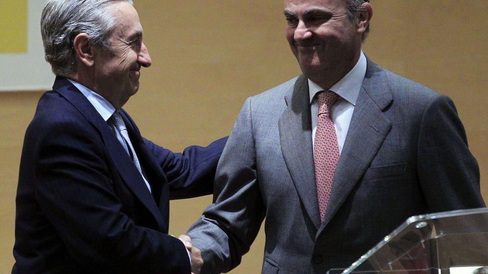 Foto: Saludo entre Marín Quemada, presidente de la CNMC, y Luis de Guindos. (EFE)