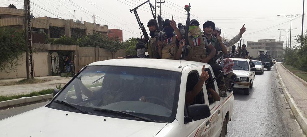 Foto: Milicianos del ISIS celebran el robo de vehículos a las fuerzas de seguridad iraquíes en Mosul, al norte de Irak (Reuters).