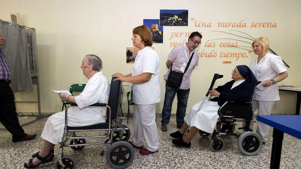 Foto: Dos personas son llevadas en silla de ruedas para ejercer su derecho al voto en las elecciones generales. (Efe)