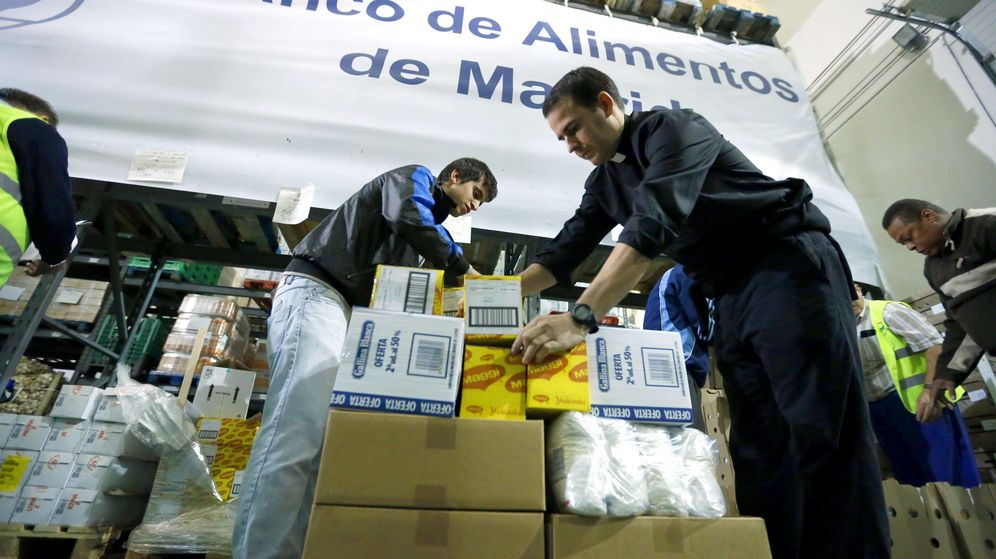 Foto: Un sacerdote acompañado de varios voluntarios trabaja en la fundación Banco de Alimentos de Madrid. (Efe)