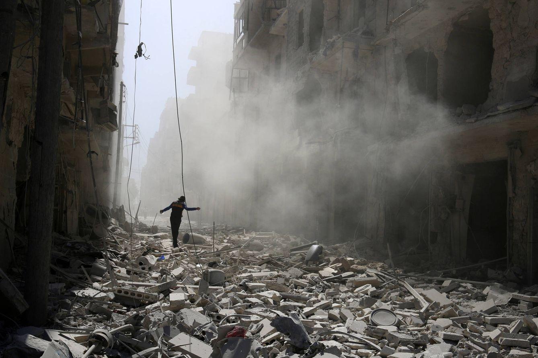 Foto: Un sirio camino sobre escombros de edificios dañados por los bombardeos en el barrio de al-Qaterji, en Alepo (Reuters).