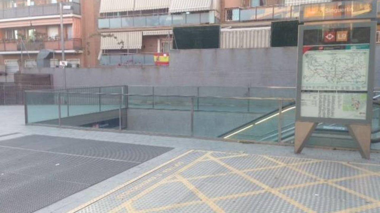 La boca de metro del barrio de Trapero, con una bandera española al fondo. (Daniel Borasteros)