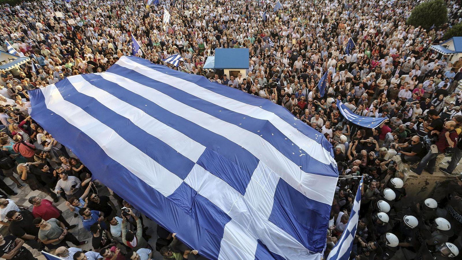 Foto: Portestas en Atenas con una bandera griega. (Reuters)