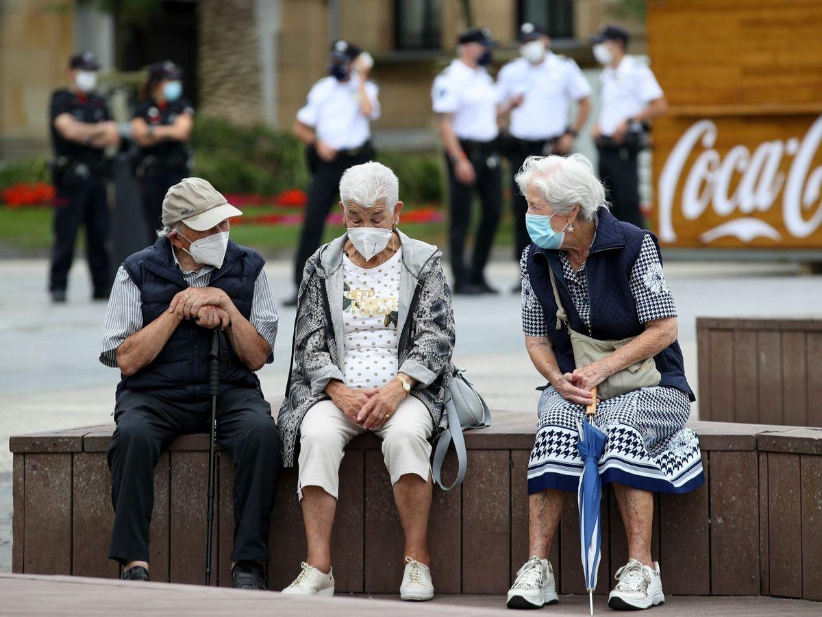 Foto: Unos ancianos conversan con mascarillas en San Sebastián. (EFE)