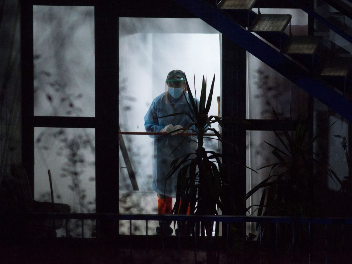 Foto: Una trabajadora sanitaria, con el equipo de protección personal, en el interior de la residencia de mayores Nosa Señora dos Milagres, de Barbadás. (EFE)