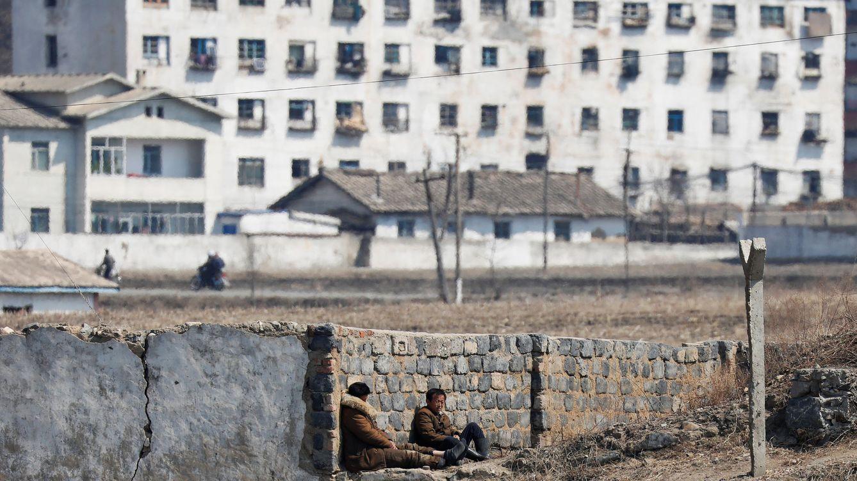 Foto: Dos hombres descansan junto a un muro en Sinuiju, en el lado norcoreano del río Yalu, en la frontera con China, en marzo de 2017. (Reuters)