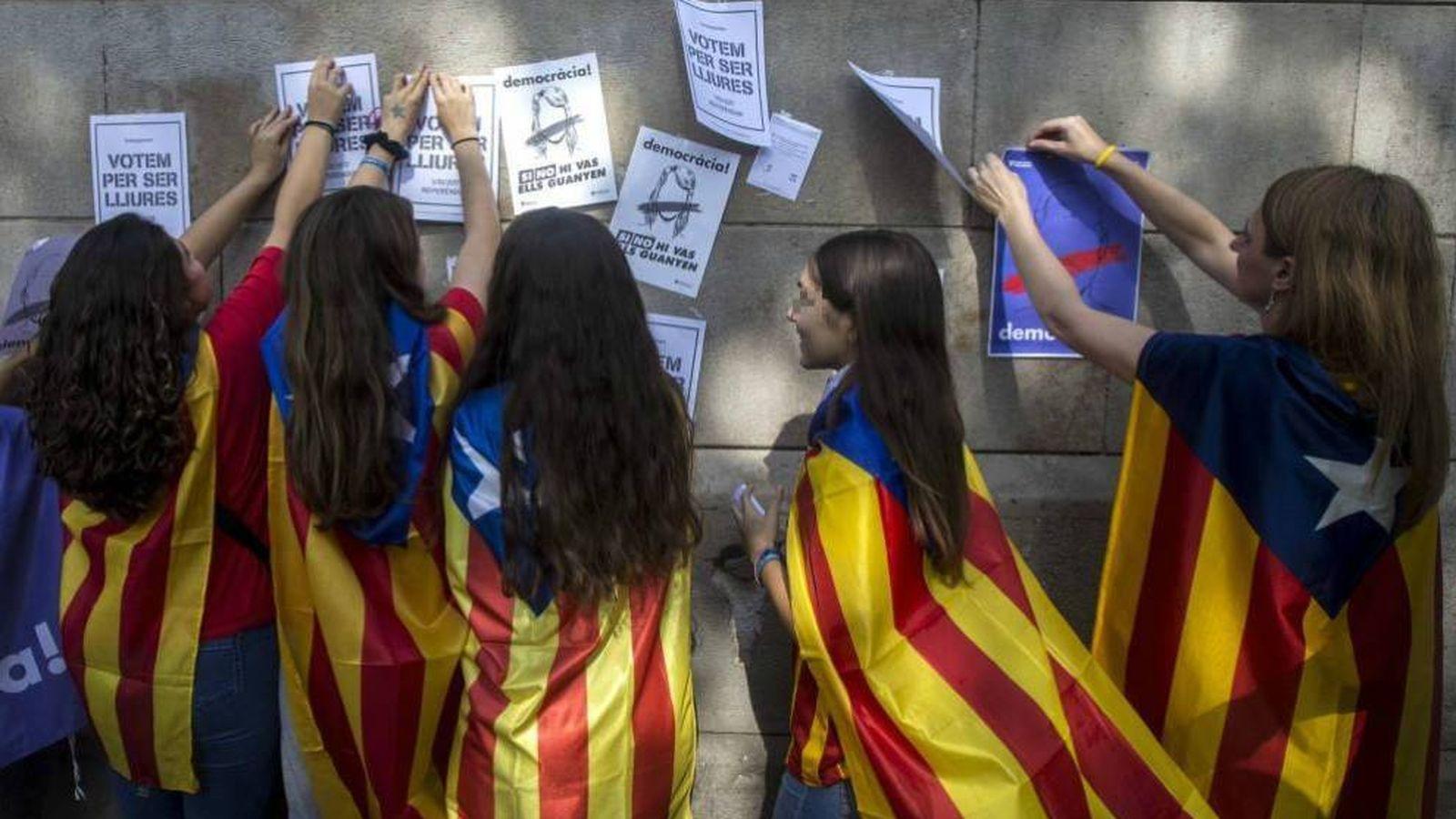 Foto: Menores de edad con esteladas cuelgan carteles a favor de votar en el referéndum del 1 de octubre. (EFE)