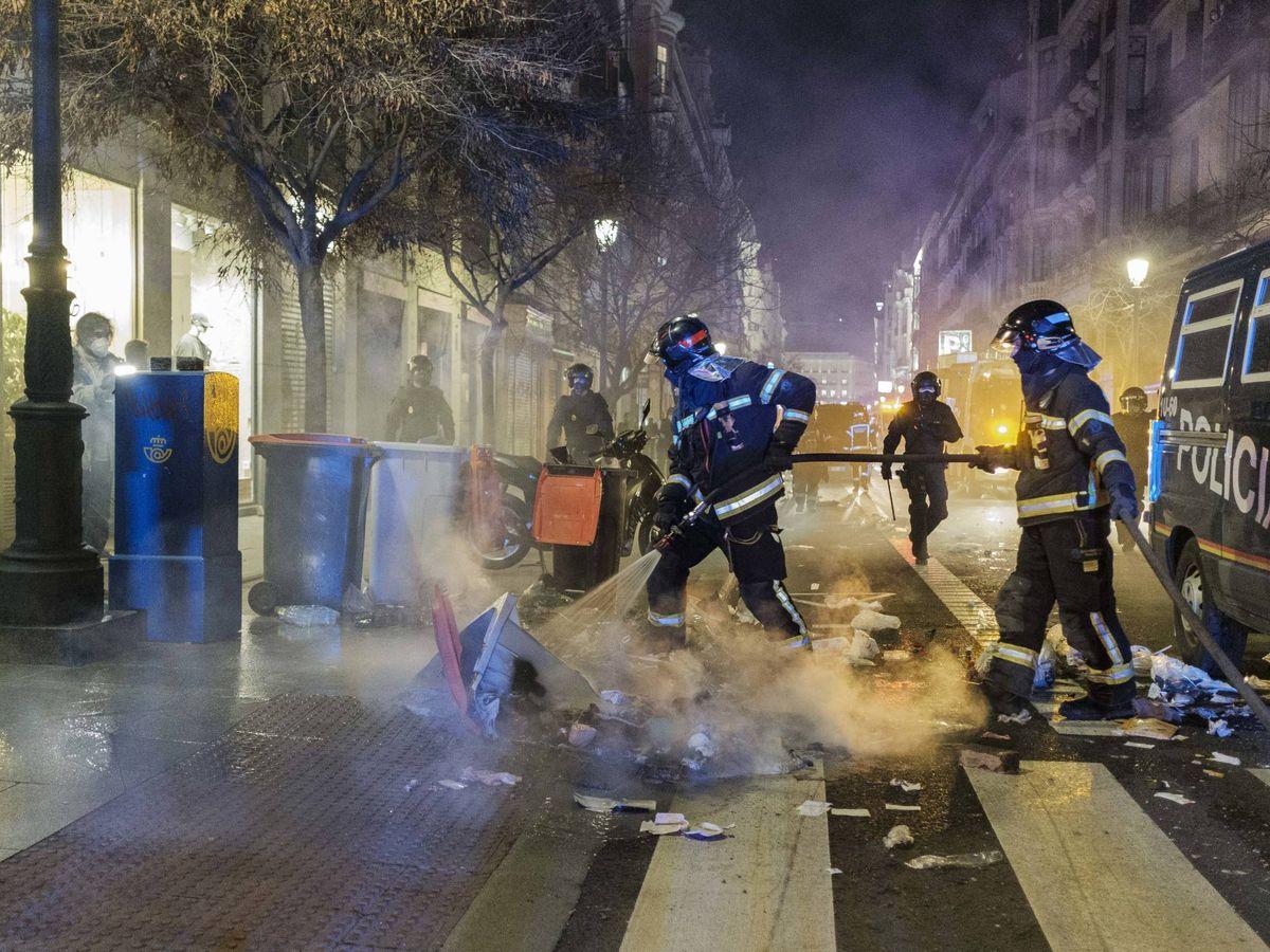 Foto: Policías nacionales sofocan un contenedor incendiado en Madrid. (Sergio Beleña)