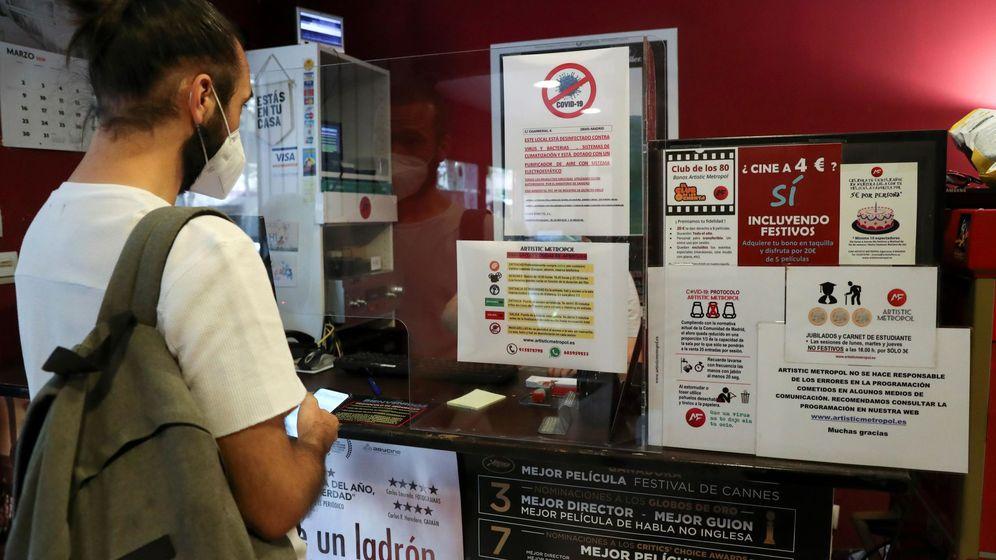 Foto: Un cliente, ataviado con mascarilla, lee las medidas de seguridad antes de entrar a una sala de cine. (EFE)