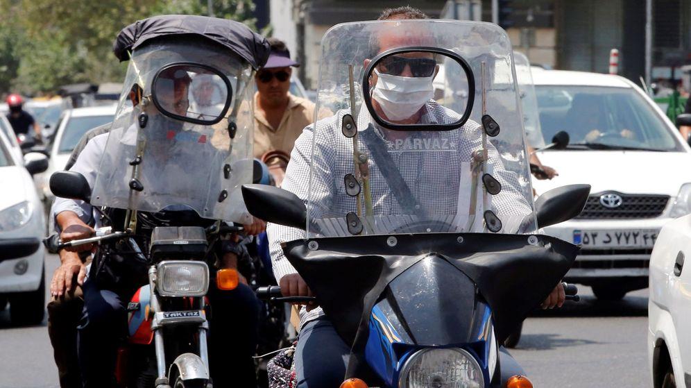 Foto: Dos motoristas protegidos con sendas máscaras circulan por una calle en Teherán, Irán. (EFE)