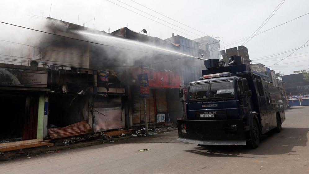 Foto: Un vehículo policial trata de apagar el fuego en una tienda incendiada en enfrentamientos entre budistas y musulmanes en Aluthgama, en junio de 2014. (Reuters)