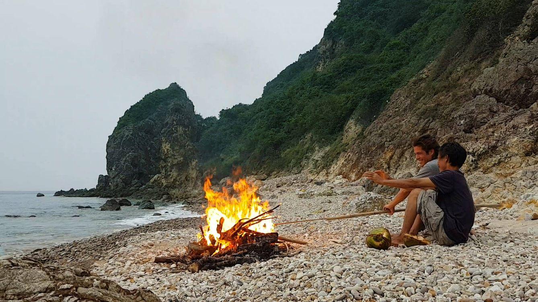 Cerezo y Lang sentados frente al fuego en la isla desierta. (Álvaro Cerezo)