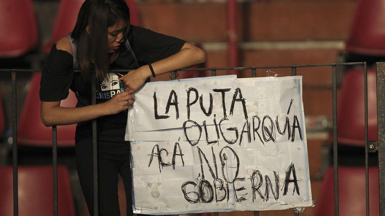 Foto: Una seguidora del candidato kirchnerista Daniel Scioli cuelga un cartel en Buenos Aires durante la jornada electoral del 25 de octubre de 2015 (EFE)