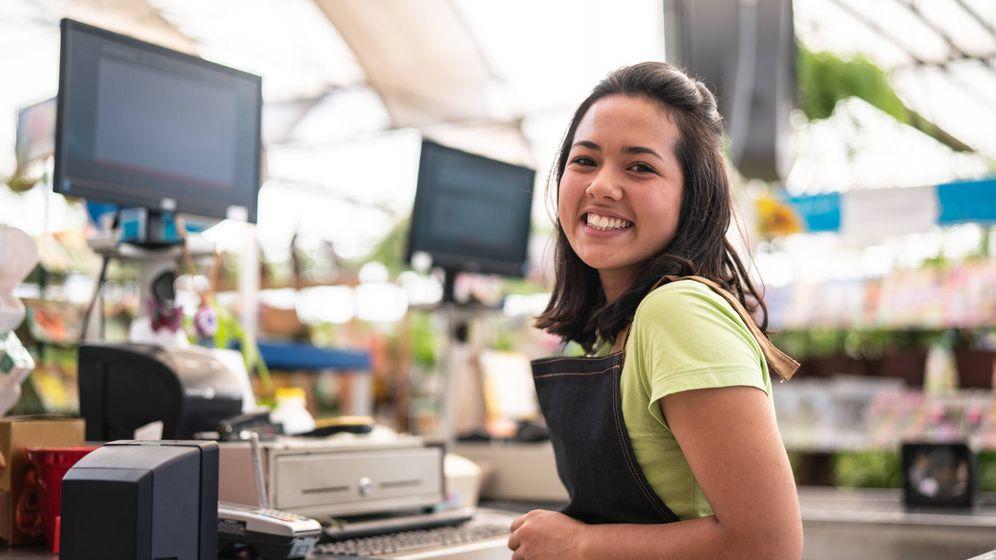 Foto: Una sonriente cajera espera que le des tus productos. (iStock)