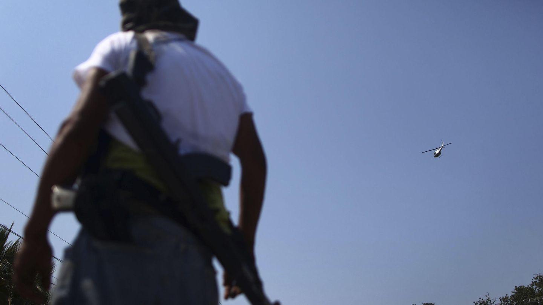 Un helicóptero de la Policía sobrevuela a un miembro de las autodefensas en Apatzingan (Reuters).
